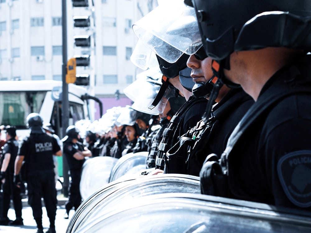 暴動鎮圧用のライオットシールドを手にする警察官